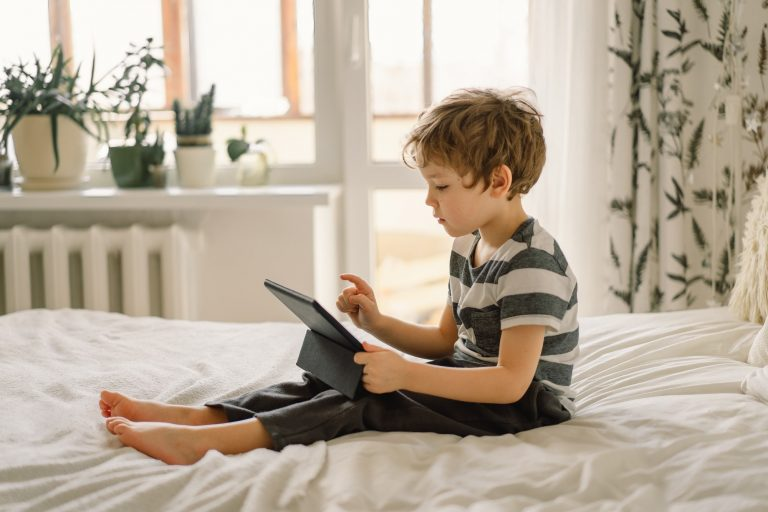 Little Boy with a tablet in the room. The boy play game on the tablet. Technology concept.