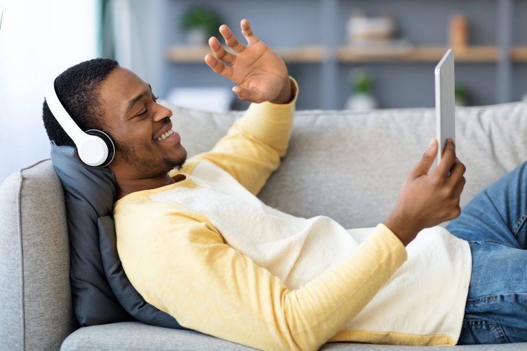Black man having video call with friends, using digital tablet
