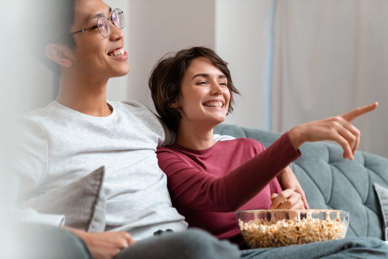 Photo of joyful couple watching videotape converter