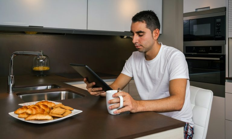 Man having breakfast and looking at home movies